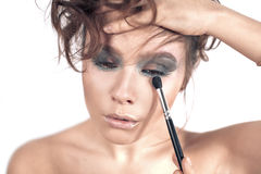 Beautiful woman applying colorful eye makeup Stock Image