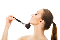Beautiful woman applying cosmetic with brush isolated Stock Photography