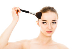 Beautiful woman applying cosmetic with brush isolated Stock Photo