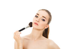 Beautiful woman applying cosmetic with brush isolated. Beautiful woman applying cosmetic with brush Stock Images