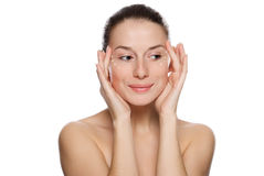 Beautiful woman applying cosmetic cream. Beautiful sexy woman applying cosmetic cream on skin near eyes. Isolated on white background Royalty Free Stock Image