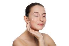 Beautiful woman applying cosmetic cream Royalty Free Stock Photos