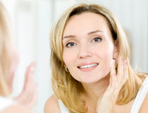 Beautiful woman applying cosmetic cream on face Royalty Free Stock Images