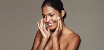 Beautiful woman applying cosmetic cream to her face Royalty Free Stock Photo