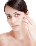 Beautiful woman applying cosmetic cream treatment on her face. Stock Photo