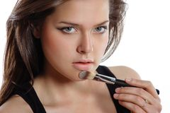 Beautiful woman applying cosmetic. Make-up Stock Images