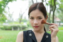Beautiful woman applying cosmetic with makeup brush on face. royalty free stock photo