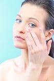 Beautiful woman is applying cosmetics Royalty Free Stock Photos