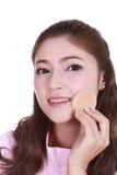 Beautiful woman applying cosmetics royalty free stock images