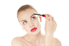 Beautiful woman applying cosmetics mascara brush. Royalty Free Stock Photography