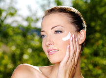 Beautiful woman applying cream on cheek Royalty Free Stock Photo