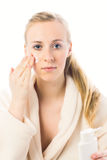 Beautiful woman applying cream on cheek. Royalty Free Stock Photos