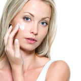 Beautiful woman applying cream Royalty Free Stock Photography