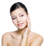 Beautiful woman applying cream on face Royalty Free Stock Photography