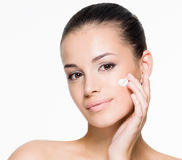 Beautiful woman applying cream on face Stock Images