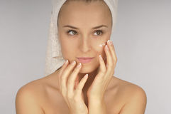 Beautiful woman applying  cream on face. Royalty Free Stock Image