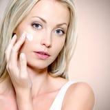 Beautiful woman applying cream on face Royalty Free Stock Image