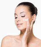 Beautiful woman applying cream on face Royalty Free Stock Image