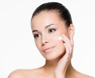 Beautiful woman applying cream on face Stock Photo