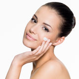 Beautiful woman applying cream on face Stock Photography
