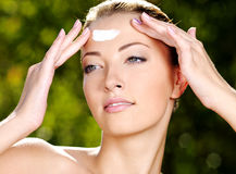 Beautiful woman applying cream on forehead. Beautiful woman with fresh health skin applying cream on forehead - Outdoors stock photo
