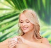 Beautiful woman applying cream Stock Photography