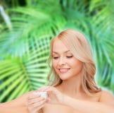 Beautiful woman applying cream Stock Photos