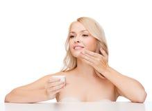 Beautiful woman applying cream on her skin Royalty Free Stock Photography