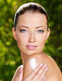 Beautiful woman applying cream on shoulder Stock Photography