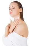 Beautiful woman applying cream on shoulder Royalty Free Stock Photo