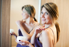 Beautiful woman applying cream on shoulder Stock Photo