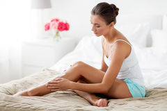 Beautiful woman applying cream to her legs at home. People, beauty, cosmetics, bodycare and spa concept - beautiful woman applying moisturizing cream to her legs Stock Photo
