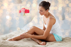 Beautiful woman applying cream to her legs at home. People, beauty, cosmetics, bodycare and spa concept - beautiful woman applying moisturizing cream to her legs Stock Photos