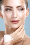 Beautiful woman applying cream treatment on her perfect face Royalty Free Stock Photos