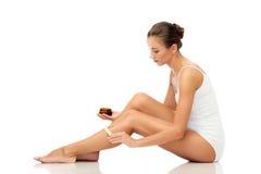 Beautiful woman applying depilatory wax to her leg Stock Photo