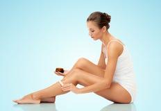 Beautiful woman applying depilatory wax to her leg Royalty Free Stock Images