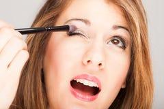 Beautiful woman applying eye shadow Stock Images