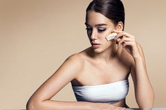 Beautiful woman applying foundation on face with sponge, skin care concept Royalty Free Stock Photography