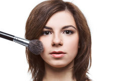 Beautiful  woman applying foundation on her face Royalty Free Stock Images