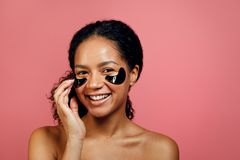 Beautiful woman applying gel patch on her face Royalty Free Stock Photos