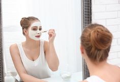 Beautiful woman applying homemade clay mask on her face at mirror stock photos