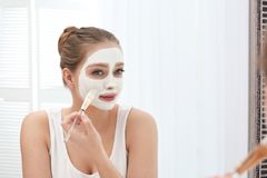 Beautiful woman applying homemade clay mask on her face at mirror royalty free stock images