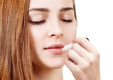 Beautiful woman applying hygienic lip balm. Over white background stock photo