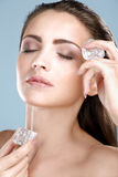 Beautiful woman applying ice cube treatment on face Royalty Free Stock Photos