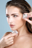 Beautiful woman applying ice cube treatment on face Stock Image