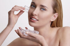 Beautiful woman applying ice cube treatment on face Royalty Free Stock Images