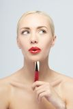 Beautiful woman applying lip gloss Stock Photo