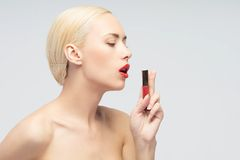Beautiful woman applying lip gloss Stock Photography