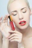 Beautiful woman applying lip gloss Stock Images