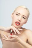 Beautiful woman applying lip gloss Royalty Free Stock Photography